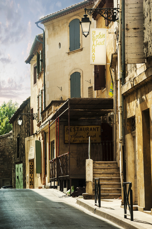 Typical street scene in Arles, Provence with an old Restaurant, given a paint effect.