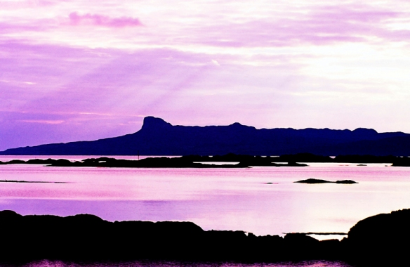 The beautiful island of Eigg, one of the Western isles of Scotland in silhouette. Photograph given watercolor treatment.