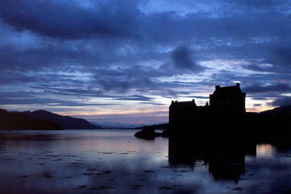 Eilean Donan Castle in the blue hour Contre-jour after sunset. Originally taken on Fuji Velvia slide film and converted to digital. Seen from the Loch Duich side with Loch Alsh in the distance.