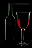 Low key photograph of a wine bottle and glass.