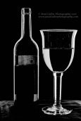 Low key photograph of a wine bottle and glass in high key monochrome.