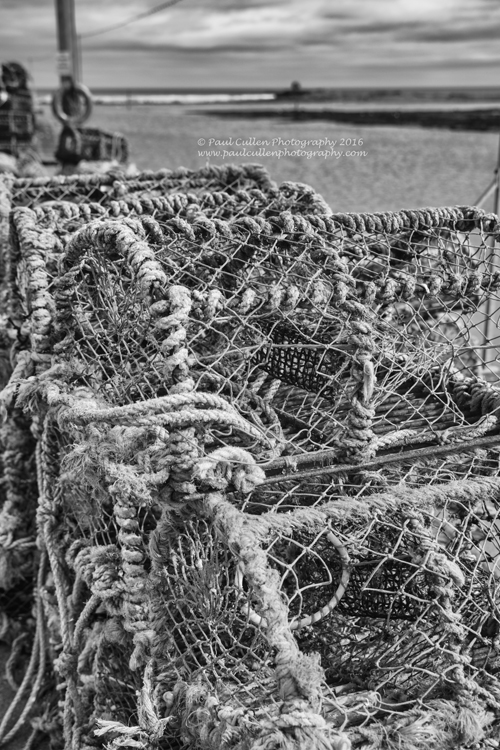 Lobster pots stacked on the quayside.